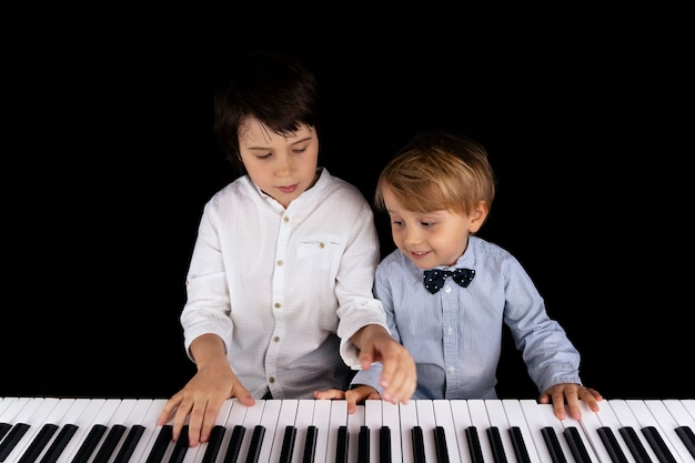Two young brothers are playing piano isolated on black