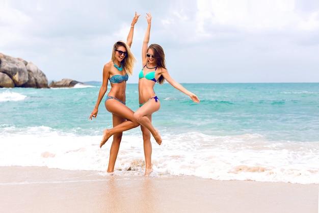 ジャンプして楽しんでいる女の子を探している2人の若いブルネットとブロンドの親友は、セクシーなスリムな体で、ビキニサングラスとファッションの明るい宝石を身に着けて、熱帯のビーチの前でポーズをとっています。