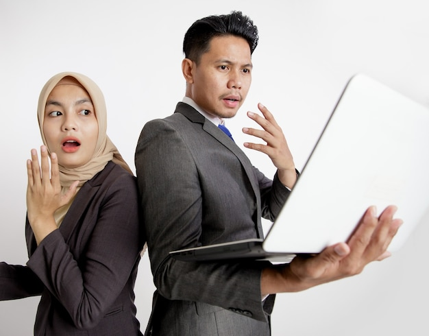 Two young business colleagues surprised looking at the laptop isolated white background
