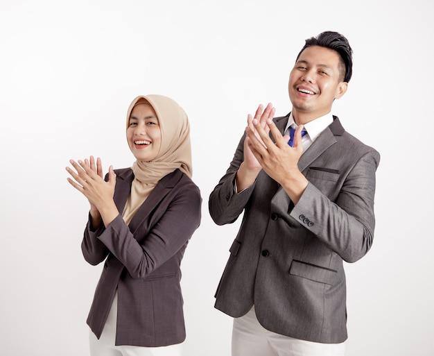 非常に興奮している2人の若いビジネスの同僚は、孤立した白い背景の誰かに拍手を与えます