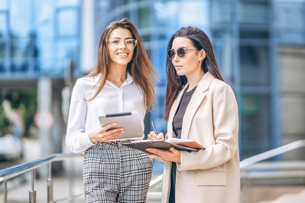Два молодых бизнес-леди с планшетом и ноутбуком, гуляя на открытом воздухе возле современного бизнес-центра.