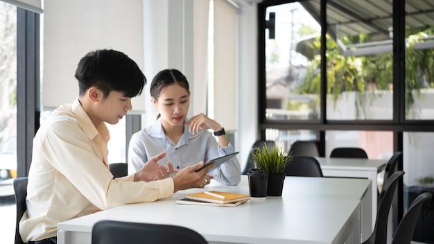 두 명의 젊은 사업가가 재무 보고서를 분석하고 현대 사무실에서 노트북 컴퓨터로 작업합니다.