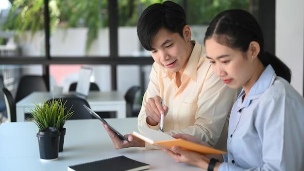 Двое молодых деловых людей вместе обсуждают новый проект в современном офисе.