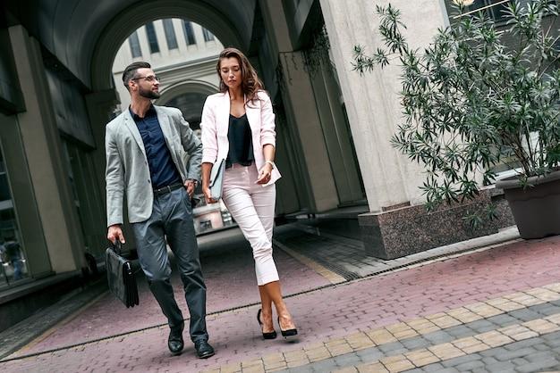 서류 가방을 들고 남자 이야기를 하는 도시 거리에서 밖에 걸어가는 두 젊은 사업가