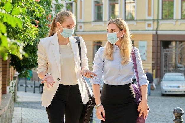 보호용 의료 마스크를 쓴 두 젊은 여성 사업가가 도시 거리를 함께 걷고 있습니다. 라이프 스타일, 전염병의 비즈니스, 전염병, 나쁜 생태