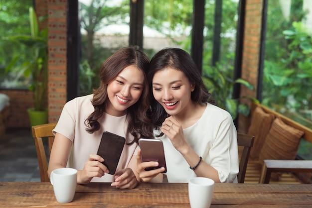 Две молодые бизнес-леди, сидя за столом в кафе. девушка показывает изображение подруге на экране смартфона