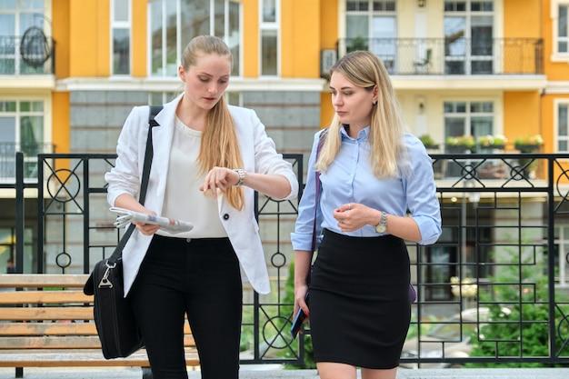 2人の若いビジネス女性が屋外を歩いて話し、街の背景、女性サラリーマン