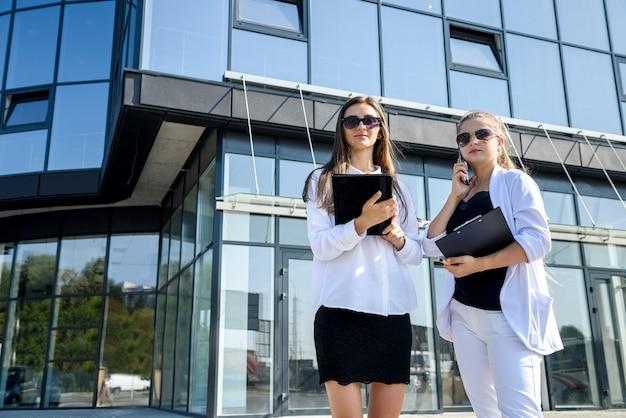 タブレットとクリップボードがビジネス センターの外でポーズをとる 2 人の若いビジネス女性