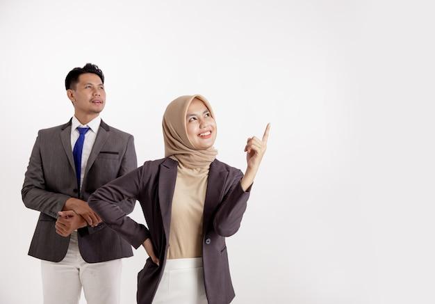 2つの若いビジネス。その方向を見ている男性と空のスペースを指している女性は、白い背景を分離