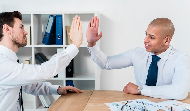 Two young businessman giving the high-five to each other at workplace