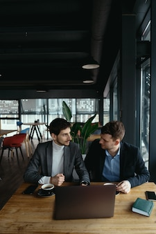 레스토랑에서 성공적인 회의 갖는 두 젊은 사업가.