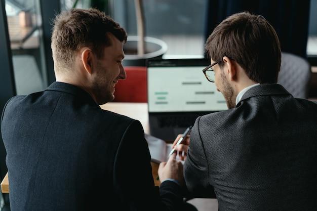 Due giovani uomo d'affari che hanno una riunione di successo al ristorante.