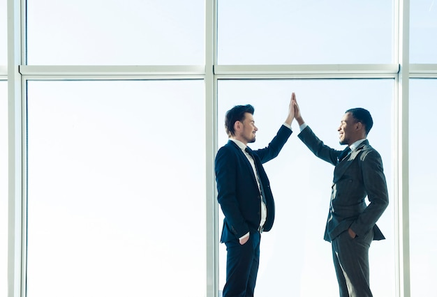 Two young businessmen are shaking hands with each other.