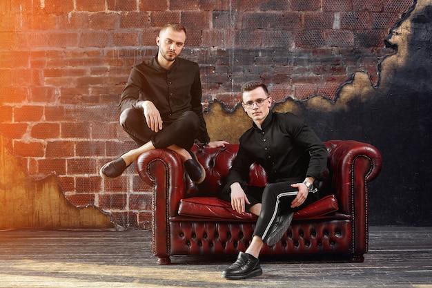 2人の若いビジネスマンがスタジオの赤い革張りのソファに座っています。若い起業家、未来の世代。独立の精神。起動
