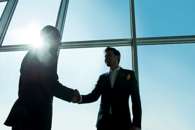 Two young businessmen are standing in office.