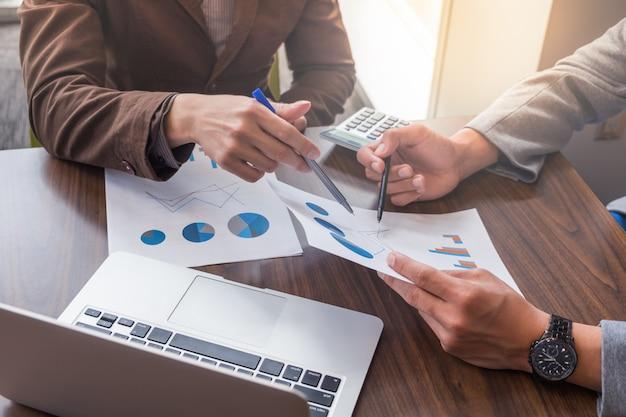 Два молодых бизнесмена обсуждают финансовые отчеты во время встречи