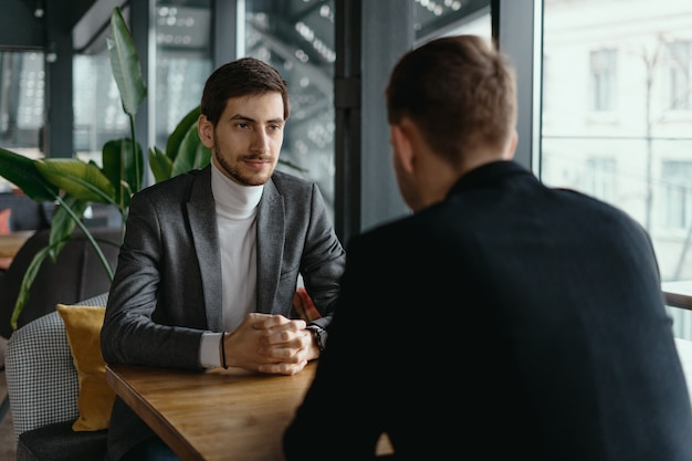 Two young businessmen discussing something
