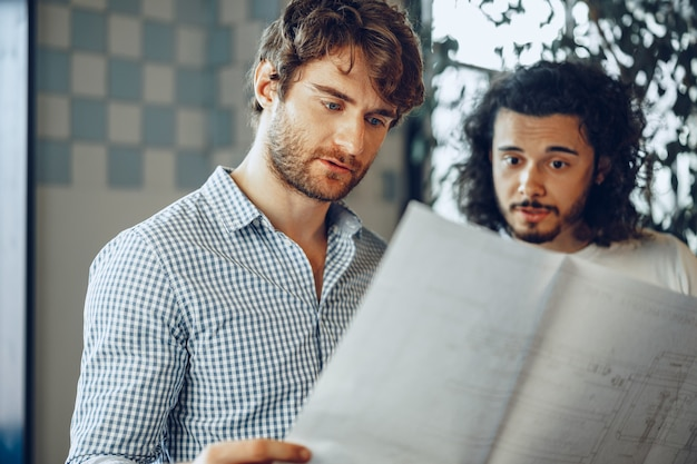 Two young businessmen looking at blueprint and discussing it