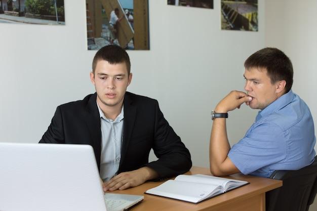 책상에 있는 컴퓨터를 진지하게 보고 있는 두 젊은 사업가.