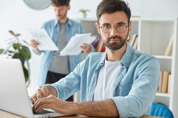 Два молодых бизнесмена продуктивно проводят утро в офисе, разрабатывают стратегию компании, работают с портативным компьютером и деловыми бумагами.
