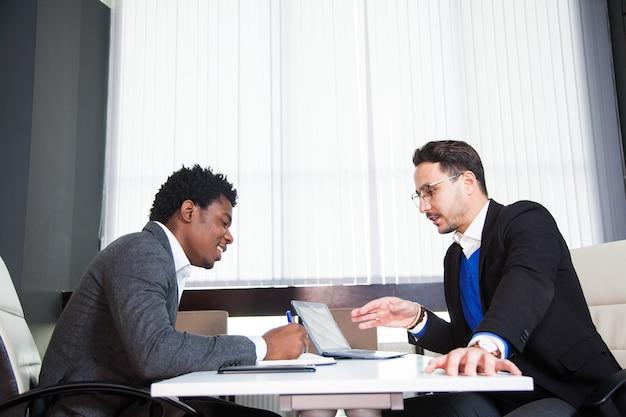 2人の若いビジネスマン、白い机