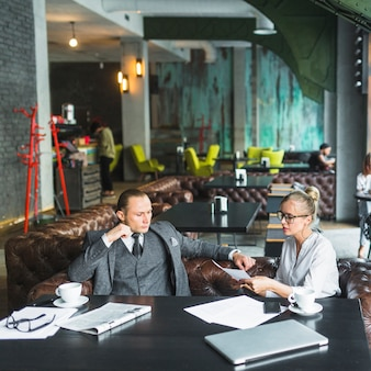 Two young businesspeople analyzing document in restaurant