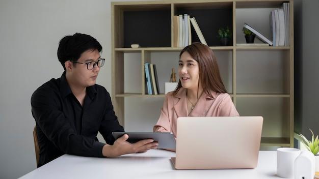 현대 사무실에서 새로운 프로젝트를 위해 만나는 두 젊은 사업가.
