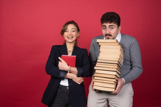 Due giovani imprenditori con libri in piedi sul muro rosso
