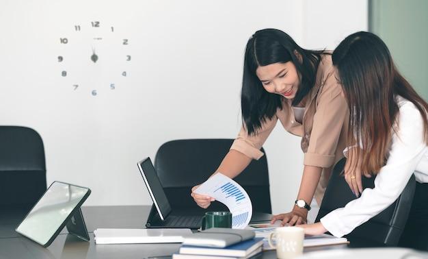 사무실 책상에 서있는 동안 사업 계획에 대해 논의하는 두 젊은 사업가