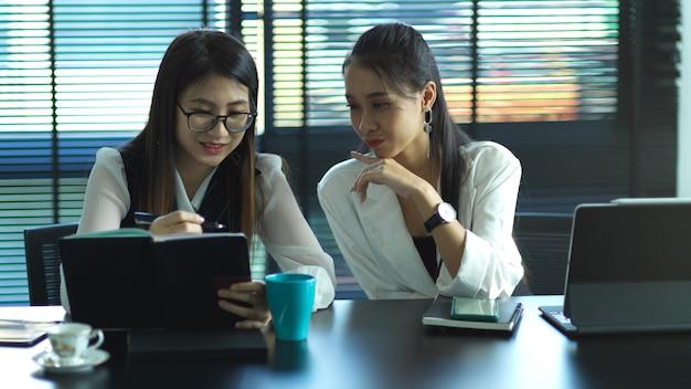 Две молодые бизнесмены вместе обсуждают проект в конференц-зале