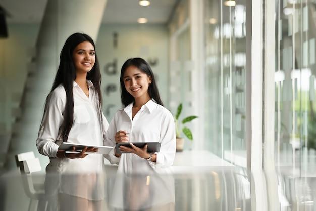現代のオフィスに立っている間タブレットを保持している2人の若い実業家の手。