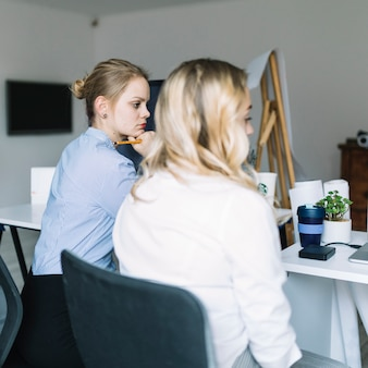 Two young businesswoman sitting seriously in the office