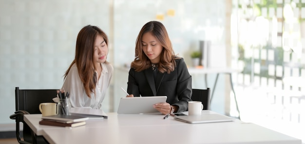 Two young businesswoman working on their strategy together while using tablet