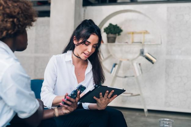 Два молодых предпринимателей, имеющих встречу в современном офисе