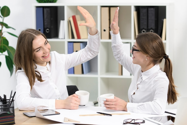 Two young businesswomen looking at each other giving high five to each other in the office