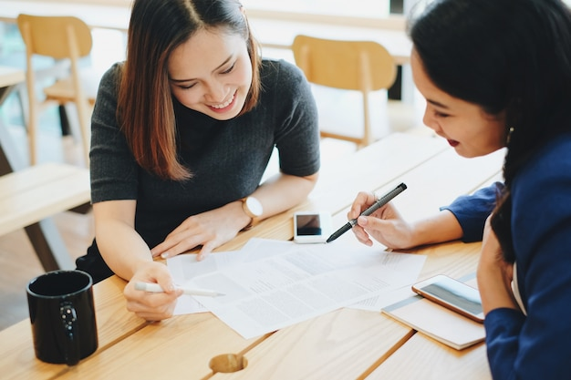 Two young businesswomen meeting and working process at the office