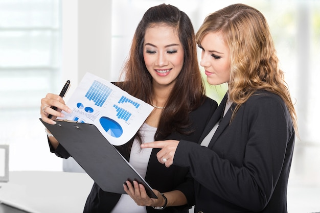 Two young businesswomen wtih a clipboard discussing