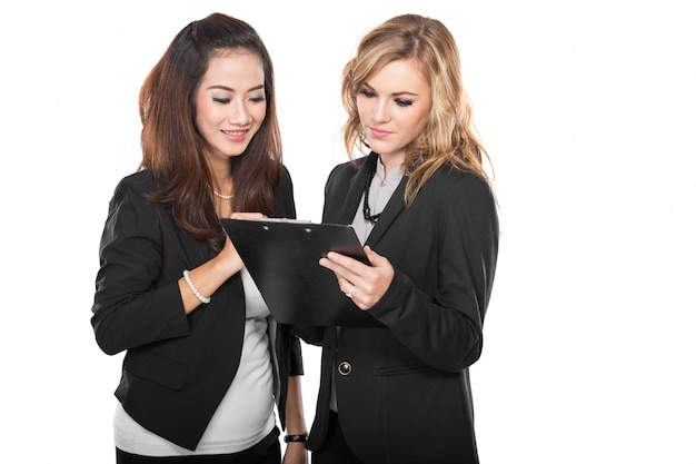 Two young businesswomen wtih a clipboard, isolated