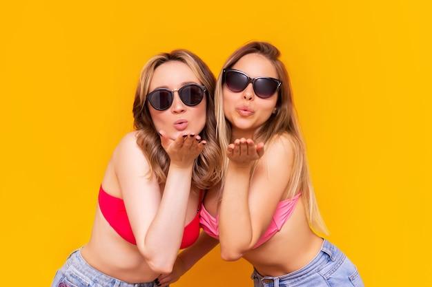 Две молодые кавказские красивые стройные женщины в купальниках, джинсовых шортах и солнцезащитных очках отправляют воздушный поцелуй с открытыми ладонями спереди на ярко-желтой стене