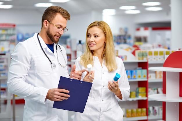 Два молодых кавказских коллеги в белых медицинских халатах, фармацевты выписывают рецепт