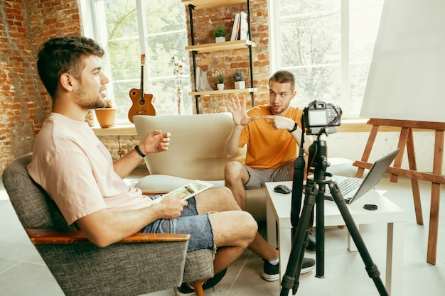 Two young caucasian male bloggers in casual clothes with professional equipment or camera recording video interview at home. blogging, videoblog, vlogging. talking while streaming live indoors.