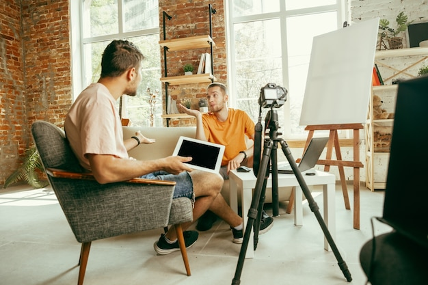 Two young caucasian male bloggers in casual clothes with professional equipment or camera recording video interview at home