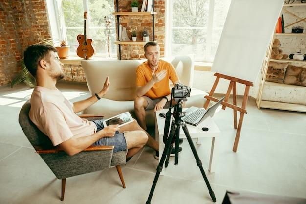 Due giovani blogger maschii caucasici in abbigliamento casual con attrezzature professionali