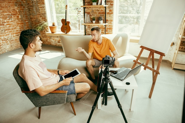 カジュアルな服装の2人の若い白人男性ブロガーが、自宅でプロの機材やカメラ録画ビデオインタビューを行っています。ブログ、ビデオブログ、ビデオブログ。屋内でライブストリーミングしながら話す。