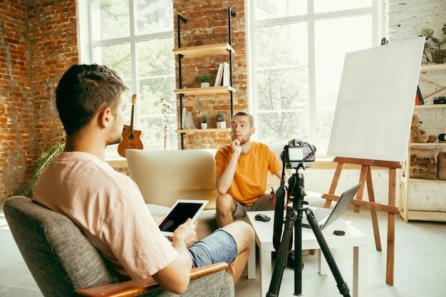 カジュアルな服装の2人の若い白人男性ブロガーが、自宅でプロ仕様の機器またはカメラ録画ビデオインタビューを行っています。ブログ、ビデオブログ、ビデオブログ。屋内でライブストリーミングしながら話す。