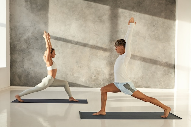 Two young caucasian people practicing yoga fitness club in the morning. attractive athletic man and blonde fit woman doing warrior one or virabhadrasana 1 on mats in gym, standing on chess order