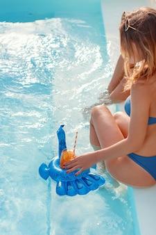 Две молодые кавказские женщины в купальниках расслабляются с тропическими коктейлями возле бассейна