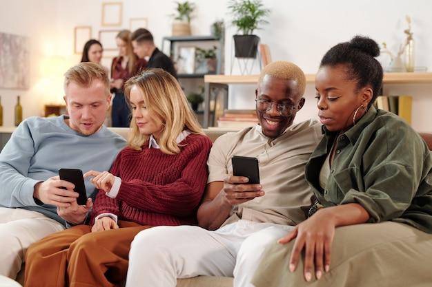 스마트 캐주얼웨어를 입고 소파에 앉아 홈 파티에서 모바일 기기로 사진이나 온라인 비디오에 대해 토론하는 두 젊은 쾌활한 커플