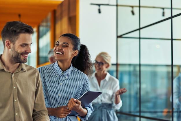 Два молодых веселых разнообразных коллег разговаривают после деловой встречи, стоя в современном