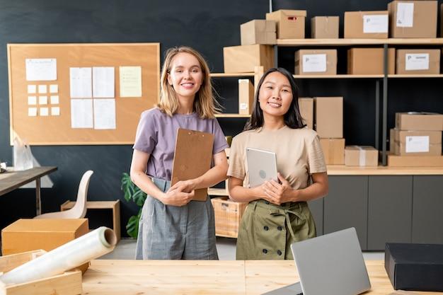 Две молодые жизнерадостные работницы офиса интернет-магазина, стоящие за столом на больших деревянных полках с упакованными коробками и доской для объявлений